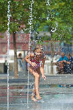 Happy girl playing in a fountain Stock Images