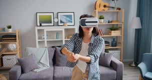 Happy girl playing game wearing virtual reality glasses in apartment alone stock footage