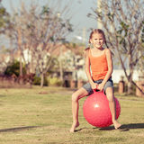 Happy girl playing with inflatable balls on the lawn. In front of house at the day time Royalty Free Stock Image