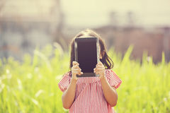 Happy Girl Playing Outdoor With Tablet Stock Photo