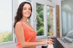 Happy girl playing piano at home Stock Photos