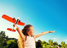 Happy girl playing with plane. Child playing with plane. Happy girl play outdoors Stock Photo