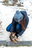 Happy girl playing with puppy. In winter outdoors Stock Images