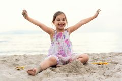 Happy Girl Playing with Sand at Beach in a Summer Evening royalty free stock images