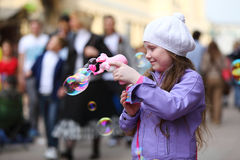 Happy girl is playing with soap bubbles gun on the street Stock Photo