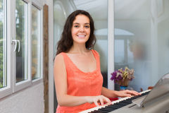 Happy girl playing synthesizer at home Stock Photos