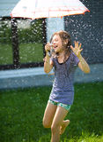 Happy girl is playing under rain Stock Photography