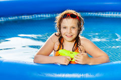 Happy girl playing with water gun in the pool Royalty Free Stock Photos