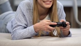 Happy girl playing with wireless joystick, game streaming hobby, lifestyle stock image
