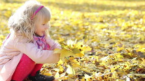 Happy girl is playing with yellow autumn maple leaves. stock video footage