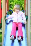 Happy girl plays on the chidish hill Stock Photos