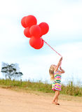 Happy girl plays with her balloons Royalty Free Stock Photos