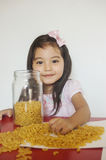 Happy girl plays macaroni stock images