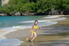 Happy girl plays in sea on tropical beach. Child on family vacation Royalty Free Stock Photos