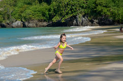 Happy girl plays in sea on tropical beach. Child on family vacation Stock Images