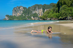 Happy girl plays in sea on tropical beach. Child on family vacation Royalty Free Stock Photo