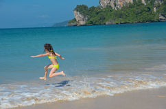Happy girl plays in sea on tropical beach. Child on family vacation Royalty Free Stock Images