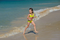Happy girl plays in sea on tropical beach. Child on family vacation Stock Photo