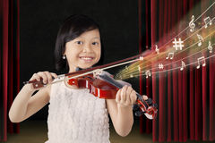 Happy girl plays violin on stage Royalty Free Stock Image