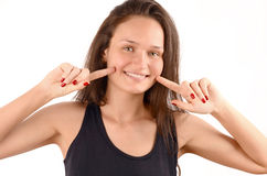 Happy girl pointing to her beautiful smile. Stock Photography