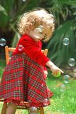 A happy girl points at bubbles floating near her Royalty Free Stock Image