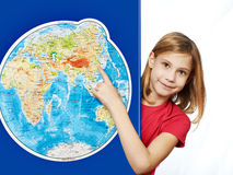Happy girl points to place on world map Stock Photo