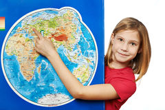 Happy girl points to place on world map Stock Image