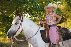 Happy girl with pony. Smiling young girl dressed in cowgirl clothes sitting on her pet pony. She has one hand on her hip Royalty Free Stock Photos