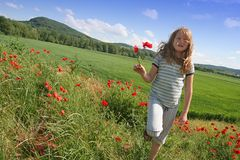 Happy girl on poppies field stock photo
