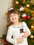Happy girl portrait in christmas decoration, playing with snowman toy, winter holiday concept, decorated fir tree and gifts Stock Photography