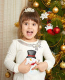 Happy girl portrait in christmas decoration, playing with snowman toy, winter holiday concept, decorated fir tree and gifts Royalty Free Stock Photos