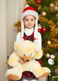 Happy girl portrait in christmas decoration, winter holiday concept, decorated fir tree and gifts Stock Image