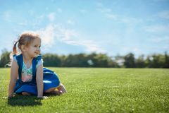 Happy girl portrait on the grass on a sunny day stock image