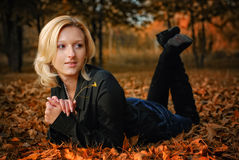 Happy girl portrait, lying in autumn leaves Stock Photos