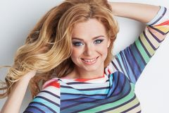 Happy girl portrait. Portrait of happy girl with long blond curly hair wearing rainbow striped sweater Stock Image