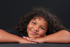 Happy girl posed on crossed hands. Portrait of a happy multi-racial girl with her head propped on her crossed hands Stock Photo