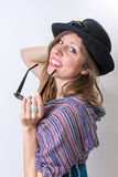 Happy girl posing with a hat and sunglasses Royalty Free Stock Photography