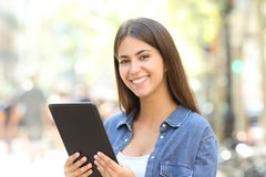 Happy girl posing holding a tablet in the street. Happy girl posing looking at camera holding a tablet in the street Stock Image