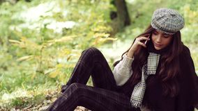 Happy girl posing with phone. Cheerful beautiful girl in sweater outdoors on beautiful fall day. Dreamy girl with long. Hair in knit sweater stock footage