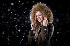 Happy girl posing in snow. Girl in a warm winter jacket posing in snow on a dark background Royalty Free Stock Image