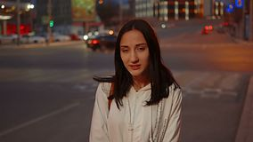 Happy girl posing in the street in front of blurred city traffic in the night stock footage