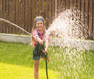 Happy girl pours water from a hose Stock Photography