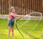Happy girl pours water from a hose Stock Photo