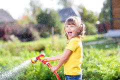 Happy girl pours water from a hose in garden Royalty Free Stock Image