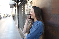Happy girl profile talking on phone in the street stock photo