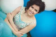Happy girl in prom with helium air balloons. Portrait of a beautiful girl graduate in a blue dress with big blue and