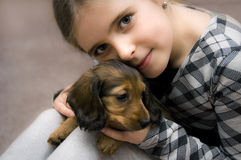 Happy girl and puppy. A small girl with puppy dog in living room Royalty Free Stock Photos
