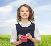 Happy girl with purse and euro coin money. Finances, childhood, people, money and savings concept - happy little girl with purse and euro coin over blue sky and Stock Photos
