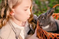 Happy girl with rabbit in the basket royalty free stock image