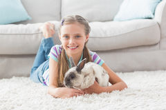 Happy girl with rabbit lying on rug in living room Royalty Free Stock Photos